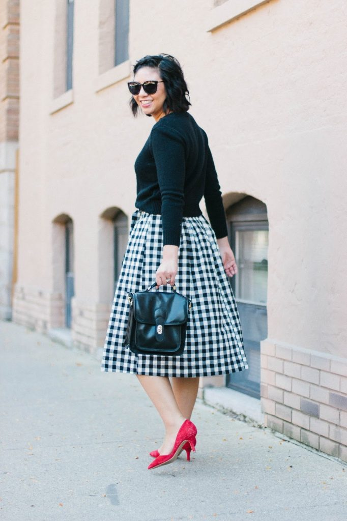 10 Things You Might Not Know About Me while wearing a gingham midi skirt and a pop of red heels