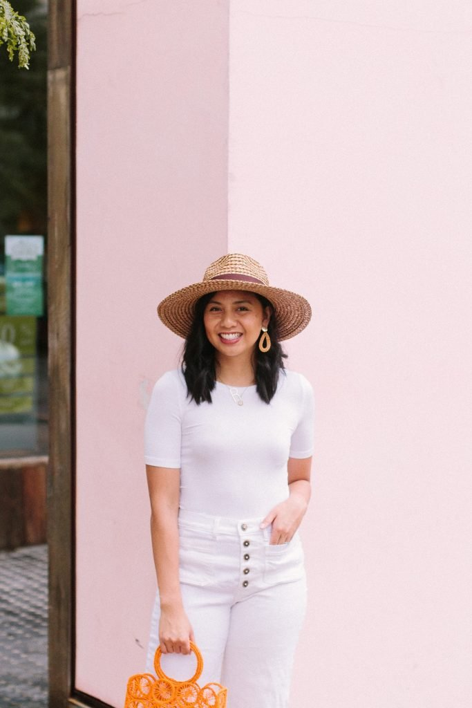 The Perfect White To Wear is this outfit that this female is wearing with a pink backdrop