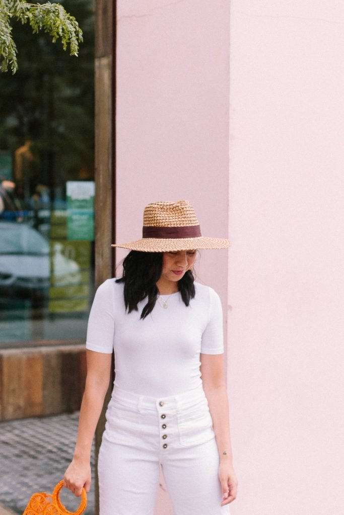 a size inclusive outfit of all white with a straw hat